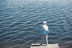 Casual man standing on quay in front of water surface at daytime. Back view of casual man standing on quay in front of water surface at daytime Stock Photos