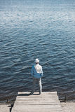 Casual man standing on quay in front of water surface at daytime. Back view of casual man standing on quay in front of water surface at daytime Royalty Free Stock Photography