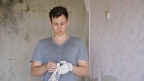 Builder putting on gloves. Casual man standing in room of renovating apartment and putting gloves on before work, slow motion stock video