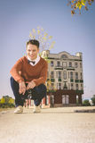 Casual man standing or squatting on the sidewalk in  old city an Stock Photography