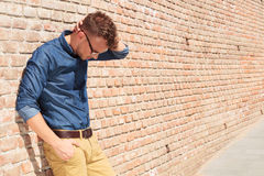 Casual man standing upset by brick wall Royalty Free Stock Photos