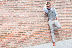 Casual man stands against brick wall Stock Photography