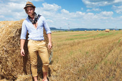 Casual man stands next to haystack royalty free stock photo