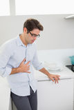 Casual man with stomach pain standing in the kitchen Stock Photo