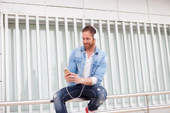 Casual man in the street listening music with his mobile. Casual guy with a denim clothes in the street listening music with his mobile Royalty Free Stock Image