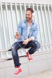 Casual man in the street listening music with his mobile. Casual guy with a denim clothes in the street listening music with his mobile Royalty Free Stock Photography