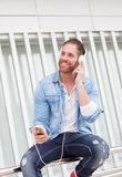 Casual man in the street listening music with his mobile. Casual guy with a denim clothes in the street listening music with his mobile Stock Photo