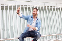 Casual man in the street listening music and taking with his mob. Casual guy with a denim clothes in the street listening music and taking a photo with his Royalty Free Stock Image