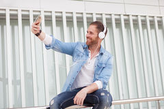 Casual man in the street listening music and taking with his mob. Casual guy with a denim clothes in the street listening music and taking a photo with his Stock Photo