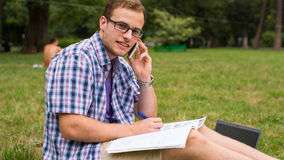 Casual man studying outdoors with a notebook. Stock Photos