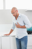 Casual man suffering from chest pain at home Royalty Free Stock Photo