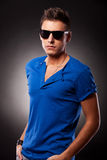 Casual man in suglasses and hands in pockets. Young casual man posing with his hands in his pockets while wearing sunglasses. He is standing at a 45 degree angle Stock Photo