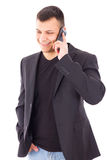 Casual man in a suit talking over mobile and smiling Royalty Free Stock Images