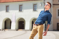 Casual man sun bathes. Casual young man bathing in the sun with a hand in his pocket in a city square Stock Photo