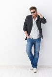 Casual man in sunglasses. Casual young man wearing sunglasses, standing over white background Royalty Free Stock Image