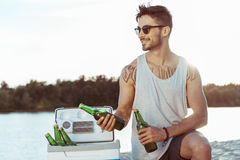 Casual man in sunglasses holding bottles of beer on riverside Royalty Free Stock Photo