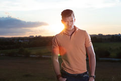 Casual man with sunset behind looks at you Royalty Free Stock Image