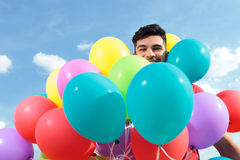 Casual man surrounded by baloons Stock Images