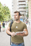 Casual man with tablet computer in the street looking away. Royalty Free Stock Image