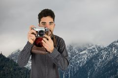 Casual man taking a photo in front of snow-covered mountains Stock Photography