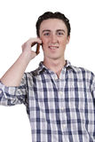 Casual man talking on a cell phone. Isolated casual man with his hand in pocket talking on the phone Royalty Free Stock Images