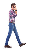 Casual man talking on the phone and walking Royalty Free Stock Photos