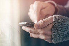 Casual man texting message on smartphone, morning sunlight throu. Gh window, male hands using mobile phone device, selective focus with shallow depth of field Stock Image