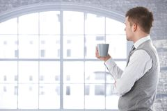 Casual man thinking front of window Stock Photography