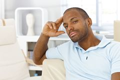 Casual man thinking in living room Stock Images