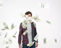 Casual man throwing Money Into Air. Over gray background stock image