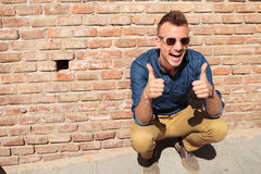 Casual man thumbs up by wall Royalty Free Stock Photography
