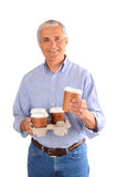 Casual man with tray of coffee cups. Casual middle aged man with a tray of to-go coffee cups. Vertical format over a white background Stock Photography