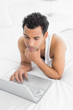 Casual man using laptop in bed Stock Photography