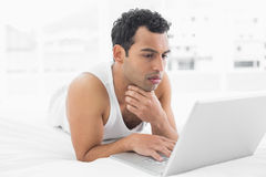 Casual man using laptop in bed Royalty Free Stock Image