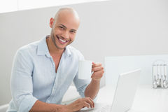 Casual man using laptop while drinking coffee at home Stock Photography