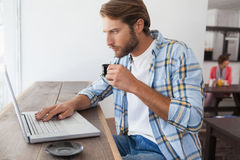 Casual man using laptop drinking espresso Stock Images