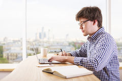 Casual man using laptop side Stock Images