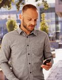 Casual man using mobile outdoors Stock Photo
