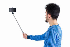 Casual man using a selfie stick Royalty Free Stock Photography