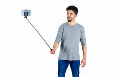 Casual man using a selfie stick Royalty Free Stock Images