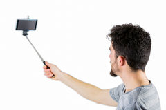 Casual man using a selfie stick Stock Photography