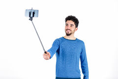 Casual man using a selfie stick Stock Image
