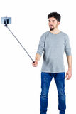 Casual man using a selfie stick Royalty Free Stock Image