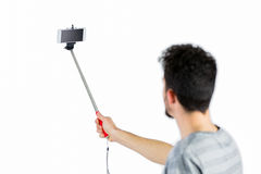 Casual man using a selfie stick Royalty Free Stock Photos