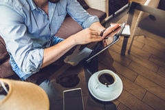 Casual Man Using Tablet Computer Sitting in Cafe Surfing Internet Royalty Free Stock Image