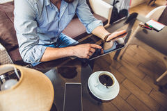 Casual Man Using Tablet Computer Sitting in Cafe Surfing Internet. A man sitting in a cafe with tablet. Casual Man Using Tablet Computer Sitting in Cafe Surfing Royalty Free Stock Images