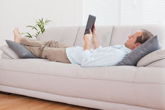 Casual man using tablet on the couch Royalty Free Stock Images