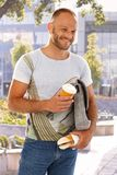 Casual man walking with coffee and sandwich Royalty Free Stock Photography