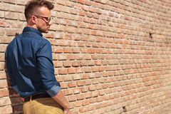 Casual man by wall back view Royalty Free Stock Photography
