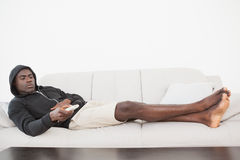Casual man watching tv on his sofa Royalty Free Stock Images